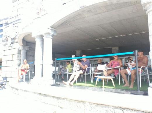 Público adulto leyendo en la biblioteca de la Playa de la Concha